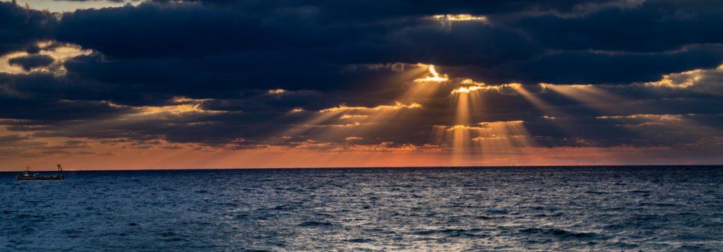 Illustrasjonsbilde som viser et rolig hav med solen som skinner gjennom tunge skyer.